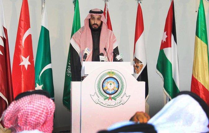 """Saúdskoarabský ministr obrany, Mohammed bin Salman, oznamuje na tiskové konferenci vznik """"Islamic Military Alliance"""". Vlevo od něj vlajka Pákistánu, který v té době ještě netušil, že je členem této aliance."""